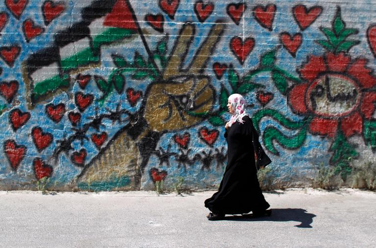 A Palestinian woman walks by a mural in Bethlehem