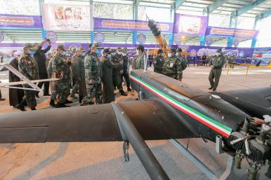 Iranian military leaders inspect drones.