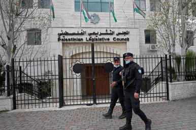 Police walk past the Palestinian Legislative Council in Ramallah
