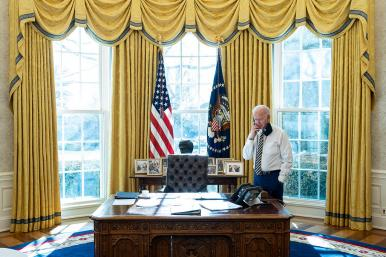 President Joe Biden speaks on the phone in the Oval Office of the White House