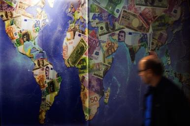 A man walks by a mural of international currencies