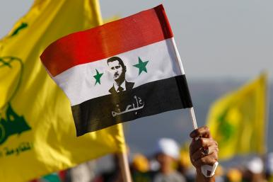 Protesters hold Syrian and Hezbollah flags