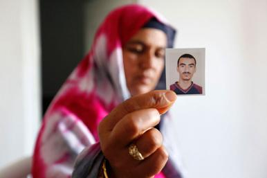 A Tunisian woman holds a photo of a relative who joined a jihadist movement